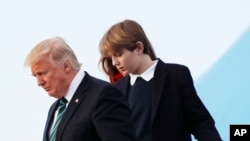 In this photo taken March 17, 2017, Barron Trump, with his father President Donald Trump and mother, first lady Melania Trump, disembark from Air Force One upon arrival at Palm Beach International Airport in West Palm Beach, Fla.
