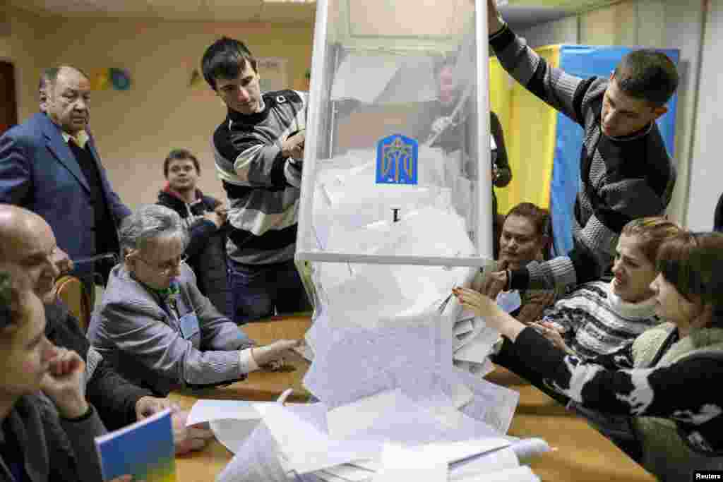 Members of a local election commission empty a ballot box at a polling station after voting in Kyiv, Oct. 26, 2014.