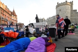 Royal fans are seen sleeping on the pavement having spent the night outside of Windsor Castle, the location for the forthcoming wedding of Britain's Prince Harry and his fiancee Meghan Markle, in Windsor, Britain, May 18, 2018.