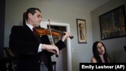 Musicians David Shenton and Erin Shields perform inside their home in the Queens borough of New York on March 30, 2021.