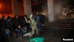 Người biểu tình ném đá trong lúc tìm cách xâm nhập vào một tòa nhà chính phủ có cảnh sát chống bạo động bên trong ở Kyiv, ngày 26 tháng 1, 2014.