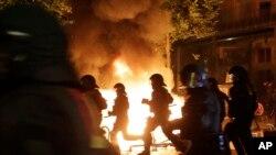 德国汉堡反G20峰会抗议火光中警察的侧影 (2017年7月6日)