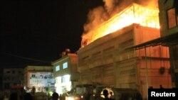 Pemberontak Suriah berusaha memadamkan kobaran api setelah serangan artileri pasukan Suriah menghantam gedung di distrik Saqba, pinggiran Damaskus.