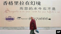 A Chinese man walks past a billboard for a new commercial development which reads 'Shangrila is in your mind but your buffalo is not' in Beijing (file photo)