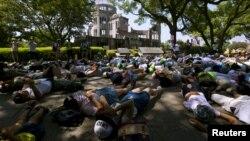 Anak-anak sekolah Jepang melakukan aksi teatrikal berpura-pura sebagai korban bom atom di depan 'Kubah Bom Atom' di kota Hiroshima, Rabu (5/8).