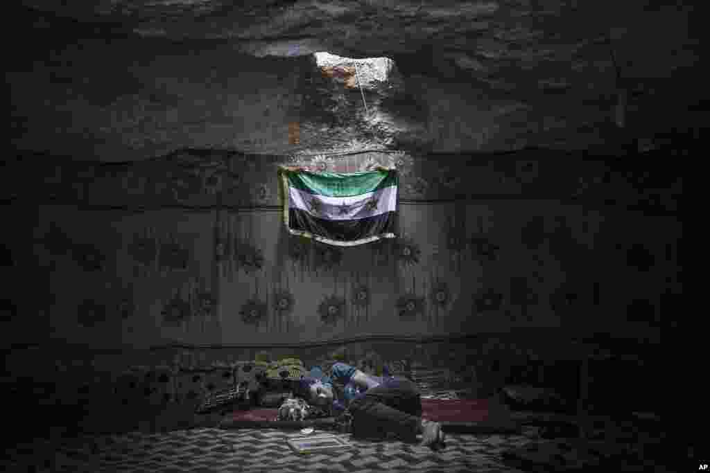 A Syrian opposition fighter rests inside a cave at a rebel camp in the Idlib province countryside, Sept. 17, 2013.