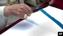 FILE - Pope Francis follows in the footsteps of his predecessor, Pope Benedict XVI, seen here signing a book during a visit to the Ardeatine Caves Memorial in Rome, March 27, 2011.
