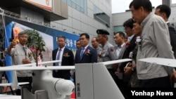 23일 대전 대덕구 유콘시스템㈜에서 열린 '대대 정찰용 무인항공기 초도생산 출고식'에서 유콘시스템 관계자가 한국 방위사업청, 군 관계자 등 참석자들에게 무인기 '리모아이-002B'에 대해 설명하고 있다. 이 무인기는 올해부터 2017년까지 한국 육군 1·3군지역의 최전방 보병부대와 해병대에 배치된다.