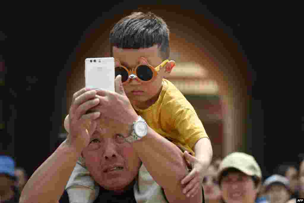 A man takes a selfie with a young boy after a visit to the Forbidden City, the former home of China's emperors, during a four-day national holiday marking May Day, in Beijing.