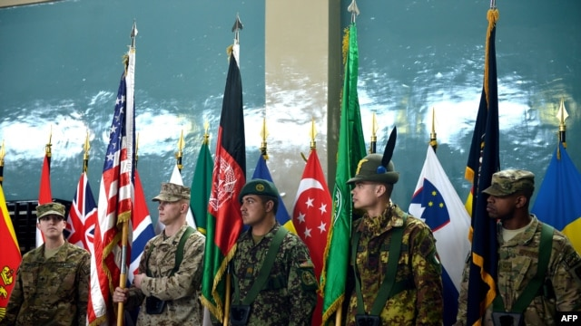 An Afghanistan National Army soldier (C) and ISAF soldiers hold flags during a change of command ceremony at the ISAF headquarters in Kabul on February 10, 2013.