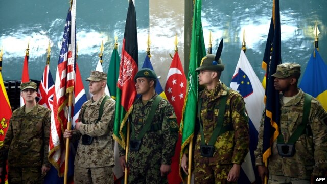 "An Afghanistan National Army soldier (C) and ISAF soldiers hold flags during a change of command ceremony at the ISAF headquarters in Kabul on February 10, 2013.  ""Together we're responsibly drawing down in Afghanistan,"" said Biden."