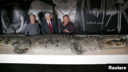 FILE - U.S. Vice President Mike Pence, center, observes a life-size replica of an Australian saltwater crocodile during his visit to the Australian Museum with Australian Foreign Minister Julie Bishop, left, and the museum's Executive Director Kim McKay in Sydney, Australia, April 22, 2017.