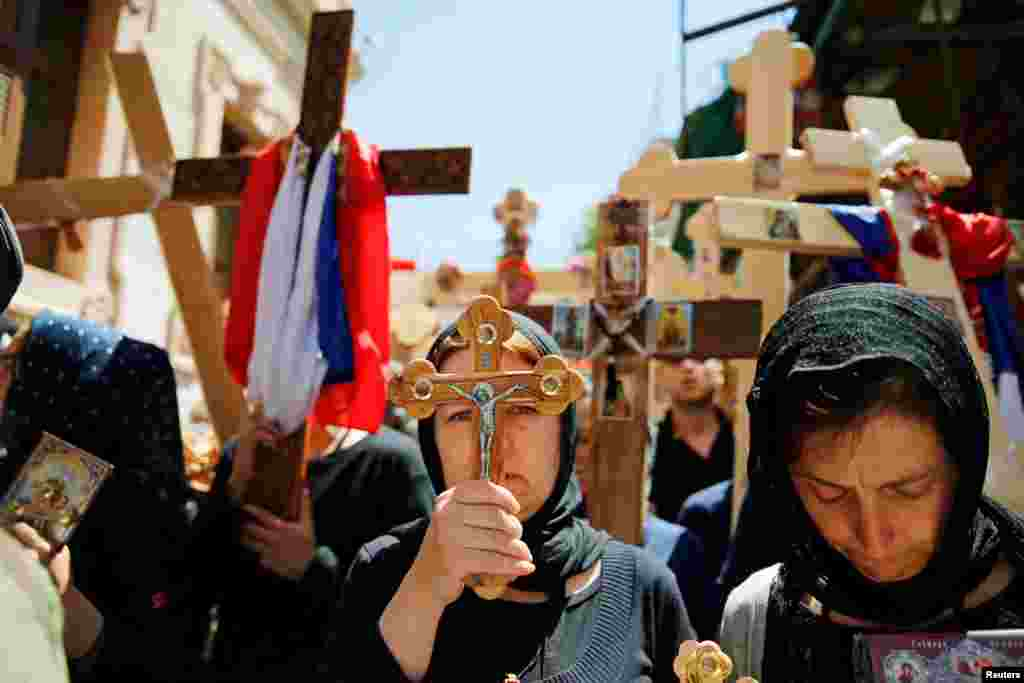 Orthodox Christian worshippers hold crosses before a procession along the Via Dolorosa on Good Friday during Holy Week in Jerusalem's Old City.