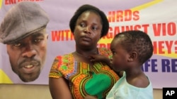 FILE - Sheffra Dzamara, wife of activist Itai Dzamara, holds her 2-year-old daughter and speaks to The Associated Press in Harare, March 8, 2016.