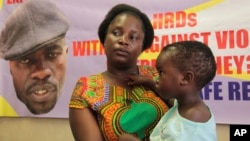 FILE - Sheffra Dzamara, wife of activist Itai Dzamara, holds her 2-year-old daughter and speaks to The Associated Press in Harare, March 8, 2016. Dzamara was pleading for the return of her activist husband, abducted by suspected state security agents a ye
