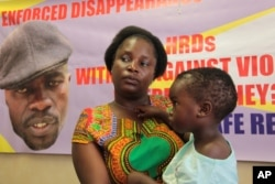 FILE - Sheffra Dzamara, wife of activist Itai Dzamara, holds her daughter and speaks to The Associated Press in Harare, March 8, 2016. Dzamara was pleading for the return of her activist husband, abducted by suspected state security agents.