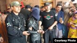 پولیس اہلکار قتل کے ملزم کو صحافیوں کے سامنے پیش کر رہے ہیں۔