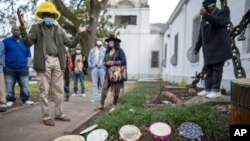"""Darryl Montana, left, the son of the late Big Chief Allison """"Tootie"""" Montana, joins others at the blessing of the tambourines outside St. Augustine Catholic Church for the start of Twelfth Night in New Orleans on Wednesday, Jan. 6, 2021. (Chris Granger)"""