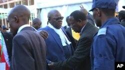 Chini ya ulinzi mkali maafisa wa chama cha upinzani wakiwa wanapekuliwa wakati walipowasili mahakamani mjini Harare, Zimbabwe kusikiliza kesi ya uchaguzi waliofunguwa kupinga matokeo ya uchaguzi, Jumatano, Agosti 22, 2018,.