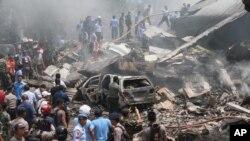 30일 인도네시아 수마트라섬 메단에 군 수송기가 추락한 가운데 경찰과 소방대가 사고 현장을 수색하고 있다.