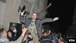 Para pemberontak Suriah mengelu-elukan seorang tentara Suriah yang membelot (2/2). Pasukan Suriah terus meningkatkan penumpasan terhadap pemberontak.