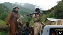 FILE - Pakistani Taliban patrol in their stronghold of Shawal in Pakistani tribal region of South Waziristan..