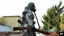 A Hungarian soldier, wearing chemical protection gear, cleans a street flooded by toxic waste.