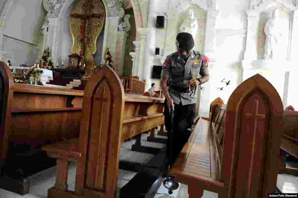 មន្ត្រីប៉ូលិសពិនិត្យមើលប្រព័ន្ធសន្តិសុខមុននឹងការប្រមូលផ្តុំនាលា្ងចថ្ងៃបុណ្យគ្រឹស្តស្មាសនៅព្រះវិហារកាតូលិក Denpasar Cathedral ទីក្រុងបាលី ប្រទេសឥណ្ឌូណេស៊ី។