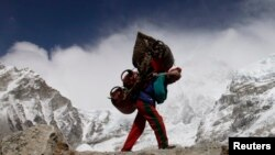 FILE - A Nepalese porter walks with his load from Everest base camp in Nepal, May 2011. Porters walk for weeks, sometimes carrying supplies heavier than their own body weight.