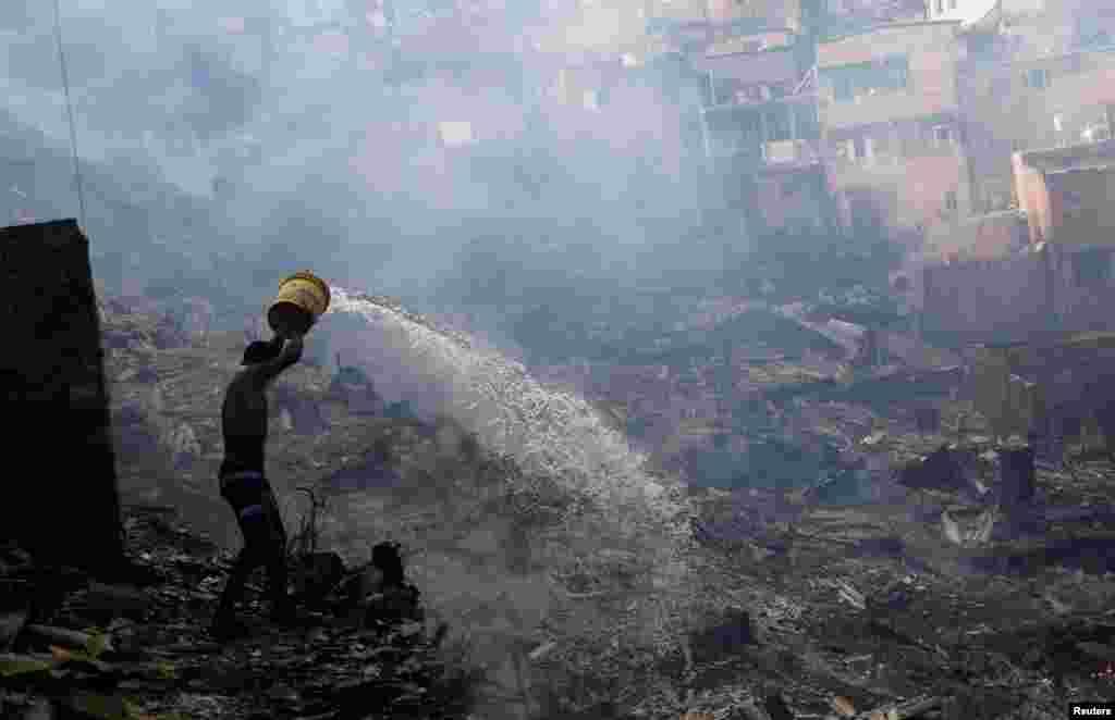 Residente tenta apagar fogo nuna favel em Paraisopolis em São Paulo, Brasil.