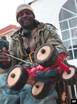 Irrepressible Zimbabwean 'recycler artist' Admire Munyuki selling toy tractors from his wheelchair at a festival in Cape Town, South Africa