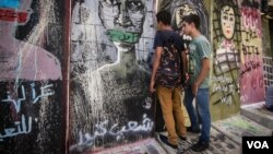 Young Lebanese peer through a gap in the wall, which was erected Monday in Beirut in the wake of clashes with protesters over the weekend. (Credit: John Owens/VOA)