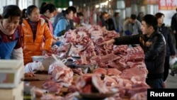 Meat stalls are seen at a market in Beijing, China, March 25, 2016. An exodus of small pig farmers in China is prolonging an industry downturn that will see the world's biggest pork producer and consumer challenge Japan as the top importer in 2016 for the first time.