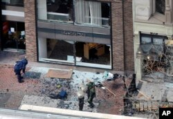 FILE - One of the blast sites on Boylston Street near the finish line of the 2013 Boston Marathon is investigated by two people in protective suits in the wake of two blasts, April 15, 2013.