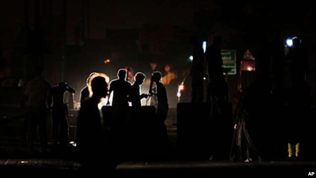 Anti-government protesters chant slogans behind makeshift barriers in the western Shi'ite village of Malkiya, Bahrain, October 6, 2011.