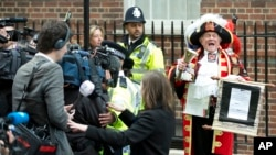 Tony Appleton, a town crier, announces to the assembled media the birth of the royal baby, outside the Lindo Wing, St. Mary's Hospital, London, Saturday, May 2, 2015.