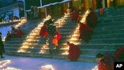 中国四川阿坝藏族羌族自治州的僧侣1月23日在一所寺庙点燃蜡烛为藏人祈福