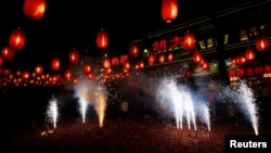 FILE - People watch fireworks to celebrate the start of the Chinese new year in front of a restaurant in Beijing, Jan. 31, 2014.