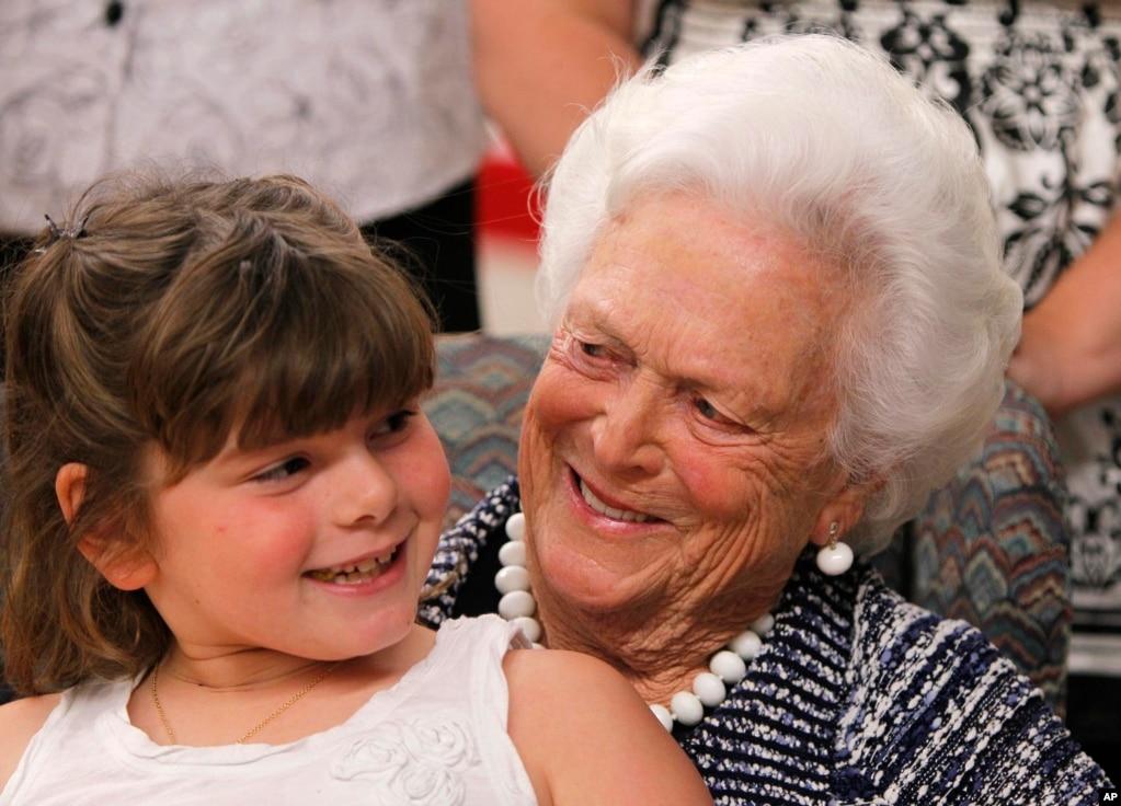 """2011年6月15日,前第一夫人芭芭拉布什在緬因州比迪福德舉行的""""識字緬因""""儀式上發表講話後,抱著一位7歲的女孩兒。 芭芭拉布什家庭掃盲基金會對高質量的家庭掃盲計劃授予贈款。 截至2011年6月,該基金會已為902個家庭掃盲計劃提供了4000萬美元。"""