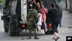 People are evacuated from the scene of an altercation involving police and an armed group in the northern Macedonian town of Kumanovo, May 9, 2015.