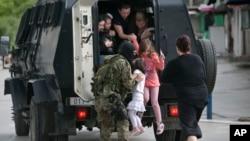 2015年5月9日警察在帮助人们从马其顿北部的库玛诺沃镇撤离。