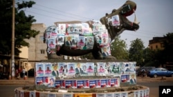 A statue of a hippopotamus is covered with election posters at a traffic circle in Bamako, Mali, Nov. 19, 2013.