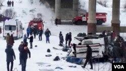 Para petugas menolong para korban luka-luka di lokasi jatuhnya bus di Sungai Kuenga, Siberia yang membeku hari Minggu (1/12).