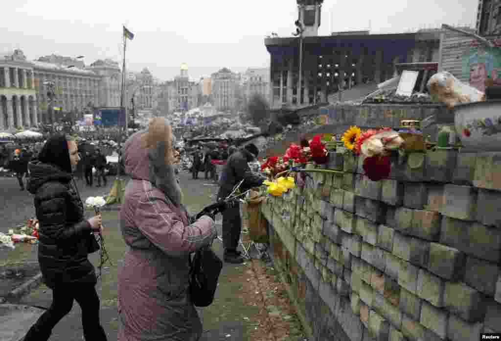 Two women prepare to place flowers on a wall in the Independence Square in Kyiv.