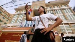 A supporter of the late Kem Ley, a prominent government critic, takes a selfie in front of the Municipal Court during the trial for Chuob Somlab, who is charged with murdering Ley, in Phnom Penh, Cambodia, March 1, 2017. REUTERS/Samrang Pring