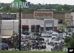 FILE - Authorities investigate a shooting in the parking lot of Twin Peaks restaurant in Waco, Texas. An indictment announced by the U.S. Attorney's Office in San Antonio accuses three Bandidos leaders of sanctioning a three-year fight that included viole