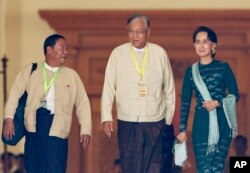Htin Kyaw, center, newly elected president of Myanmar, walks with National League for Democracy leader Aung San Suu Kyi, right, at Myanmar's parliament in Naypyitaw, Myanmar, Tuesday, March 15, 2016.