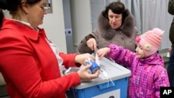 A little girl helps her mother to cast a ballot at a polling station in Tallinn, Estonia, March 1, 2015.