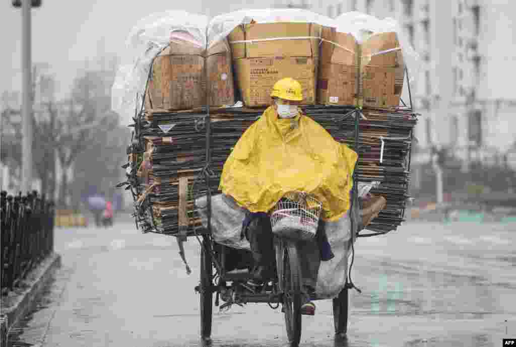A worker steers his tricycle packed with recycling papers in Shanghai, China.