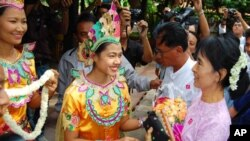 Burmese democracy icon Aung San Suu Kyi (R) receives flowers as she arrives at Bagan Hotel in Bagan, Burma, July 4, 2011